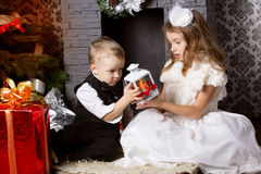 New year time. Happy childrens with cristmas presents near the fur-tree Stock Photos