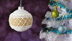 New Year toy near Christmas tree. Beautiful festive white toy ball with a pattern in winter time for the new year on a beautiful bokeh background near a white Stock Image