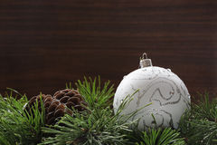 New year toys. Pine cone and new year toy on fir branches and brown wooden background Royalty Free Stock Photos