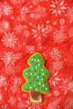New year tree cookie on the red background. Vertical. Free space. Flat. New year tree cookie green on red. Snowflakes napkins Royalty Free Stock Photography