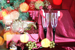 New Year tree decorations glasses. Decorated with a satin cloth festive table with glasses of wine and a dressed Christmas tree Royalty Free Stock Image
