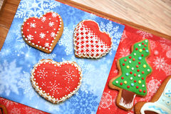 New year tree and hearts cookies in wooden desk. Flat. Horizontal. Free space. Cookies on red and blue background Royalty Free Stock Images