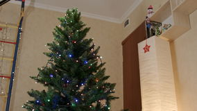 New year tree with lamp garlands in the center of the living room stock footage