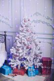 New Year tree in a modern interior with gift boxes. Delicate, light colors Royalty Free Stock Photo
