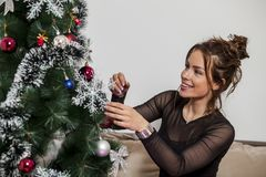 New year tree and woman. Woman decorates a new year tree Stock Photo