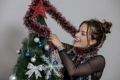 New year tree and woman. Woman decorates a new year tree Stock Photos