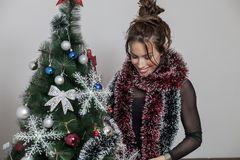 New year tree and woman. Woman decorates a new year tree Royalty Free Stock Images