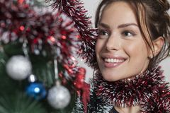New year tree and woman. Woman decorates a new year tree Stock Image