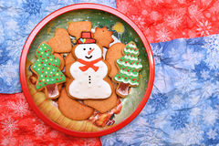 New year trees and snowman cookies in dish. Flat. Horizontal. Free space. Cookies on red and blue background Stock Photo