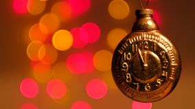 New year vintage toy gold clock on abstract christmas background. Countdown. 12 hours. New year vintage toy, gold clock on a background of holiday lights. 4k stock video