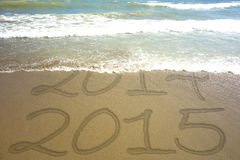 New Year 2015 Water Edge Text Sand. Wawe covering inscription 2014 on a beach sand -  new Year 2015 is coming concept Stock Images