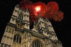 New Year at Westminster Abbey. Towers of Westminster Abbey against a  blue sky with clouds with holiday fireworks exploding in the background Royalty Free Stock Photo