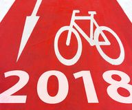 2018 New Year White graphic signs of arrow with bicycle. Symbol on a red bike path on the road royalty free stock image