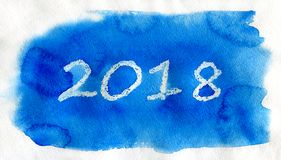 New Year 2018. White lettering on the blue watercolor background. New Year 2018. White lettering made by wax crayons on the blue watercolor background Royalty Free Stock Photos