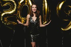 New Year. Woman With Balloons Celebrating At Party. Portrait Of Beautiful Smiling Girl In Shiny Dress Throwing Confetti stock images