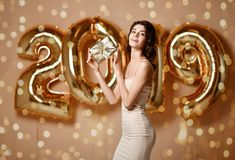 Portrait Of Beautiful Smiling Girl In Shiny Golden Dress Throwing Confetti, Having Fun With Gold 2018 Balloons On Background. royalty free stock image