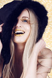 New Year woman laughing. Beautiful blond woman with gold make-up and long feather lashes, wearing winter hat laughing in a spirit of the New Year Stock Photography
