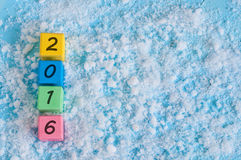 New 2016 Year wood number on color wooden cubes. With snow and empty space for text. Happy new year concept postcard Royalty Free Stock Images