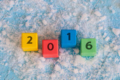 New 2016 Year wood number on color wooden cubes. With snow and empty space for text. Happy new year concept postcard Stock Images