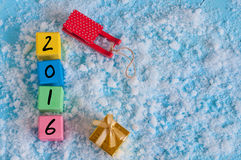 New 2016 Year wood number on color wooden cubes. With snow, sled, gift and empty space for text. Happy new year concept postcard Royalty Free Stock Images