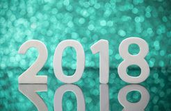 New year 2018 wood numbers reflexion on glass table over green Stock Photo