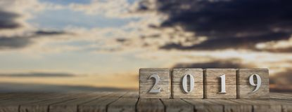 New year 2019 on wooden cubes, wooden table, sunrise background, banner, copy space. 3d illustration. New year 2019 on wooden cubes, wooden table, sky at dawn Royalty Free Stock Photos
