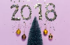 New Year 2018 writing composed of glittering confetti over Christmas tree. Stock Photo