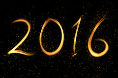 New Year 2016. Written with flames and surrounded by stars and sparks on a black background stock photography