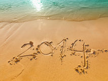 New Year 2014 written in sand on the beach Stock Photography