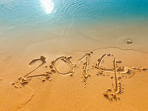 New Year 2014 written in sand on the beach Royalty Free Stock Photos