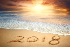 New year 2018. Year 2018 written on sand at sunrise Royalty Free Stock Photos