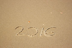 New year 2016 written in sandy beach. image is retro filtered. Stock Photos