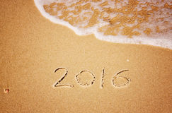 New year 2016 written in sandy beach. image is retro filtered. Royalty Free Stock Photos