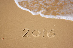 New year 2016 written in sandy beach. image is retro filtered. Stock Photo