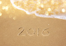 New year 2016 written in sandy beach. image is retro filtered Stock Images