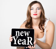 New year written on virtual screen. beautiful woman with bare shoulders holding pc tablet. technology, internet and Royalty Free Stock Images