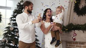 New Year, young father is blowing up a firework, sparkles of fireworks and confetti flying in the air. Cheerful family. With cute toddler at Christmas stock video footage