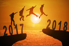 2018 new years background. Silhouette group of young mans jumping between 2017 and 2018 years with beautiful sunset at the sea-use for news year and concepts for Stock Photo