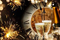 New Years background with sparklers and champagne. Festive New Years background with sparklers and champagne in front of a clock counting down to midnight with stock photos