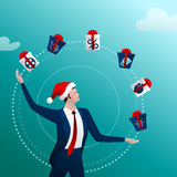 New Years businessman juggles with gifts. The businessman in a New Year cap with a happy smile juggles gift with boxes and gifts on a blue background. Concept Royalty Free Stock Photo
