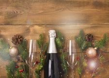 New Years Christmas Celebration Background with Pair of Wineglasses and Bottle of Champagne Christmas New Year Card Fir Decoration. Wooden Background Copy Space stock photos