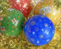 New Years, Christmas still life. Handmade decorated green, red, blau, yellow balls on the gold tinsel. Close up Stock Photo