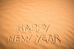 Happy New Year background. Handwriting in tropical sand. Royalty Free Stock Image