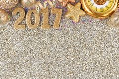 New Years Eve 2017 border over a glittery background. New Years Eve 2017 golden numbers with top border of decorations over a glittery background stock photography