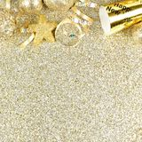 New Years Eve border on shiny gold background. New Years Eve top border of streamers and decorations over a glittery gold background Royalty Free Stock Image