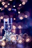 New Years Eve celebration. Background with pair of flute,candles forming the 2019 number, glitter and defocused background, with christmas tree light forming a stock images