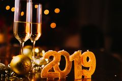 New Years Eve celebration. Background with pair of flute,candles forming the 2019 number, glitter and defocused background, with christmas tree light forming a stock image