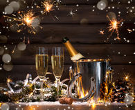 New Years Eve celebration. Background with pair of flutes and bottle of champagne in  bucket  and a horseshoe as lucky charm Royalty Free Stock Images