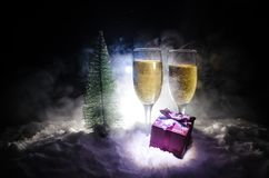 New Years Eve celebration background with pair of flutes and bottle of champagne with christmas tree on snow on dark background. Stock Photo