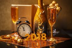 2018 New Years Eve. Celebration background with pair of flutes, bottle of champagne and a clock Stock Photos